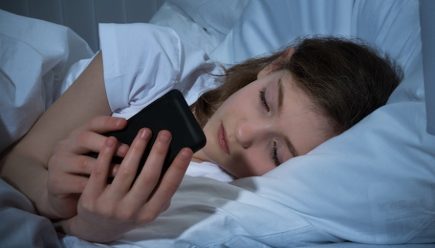 Girl Texting On Mobile Phone At Night While Lying In Bed